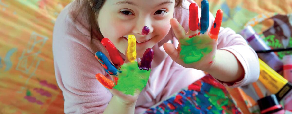Dziewczynka pokazująca pomalowane kolorowymi farbami dłonie. Grafika dekoracyjna.